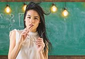 Woman With Long Hair In White Blouse Stands In Classroom. Lady Strict Teacher On Dreamy Face Stands  poster
