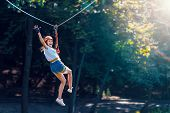 Closeup Of Female Slender Legs In White Sneakers Keep Balance On Wooden Stumps Hanging On Ropes On T poster