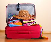 stock photo of panama hat  - Open red suitcase with clothing in the room - JPG