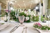 Closeup Table Setting With Plates And Tableware, Adorned With Flowers. Floral Decoration For Wedding poster