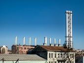Tall Factory Pipes Chimneys Of Light Industry Plant At Industrial Zone. Outdoor Image With Clear Blu poster
