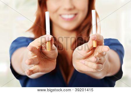 Joven sosteniendo el cigarrillo clásico de un lado y el otro cigarrillo electrónico