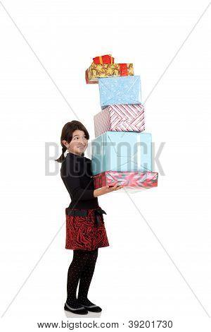 Little girl carrying huge pile of christmas presents