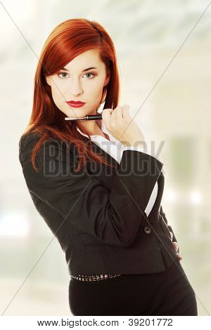 Happy business woman or student in elegant clothes holding pen, isolated on white background