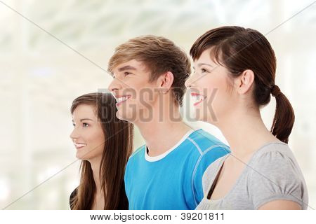 Three young happy friends. Two girls one boy smiling and looking left. Focus on male.