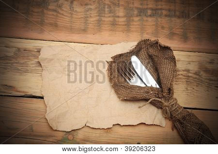 knife and fork in rough old sacking on blank paper over wood