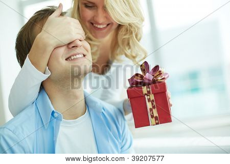 Image of young female with giftbox closing her boyfriend eyes to make a surprise for him