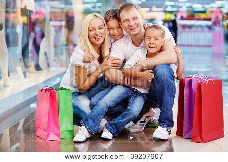 Retrato de família alegre com paperbags olhando para câmera no shopping