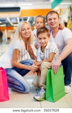 Retrato de família moderna com paperbags olhando para câmera no shopping