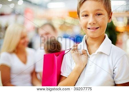Retrato de menino feliz, segurando a paperbag e olhando para câmera no shopping com os pais no fundo
