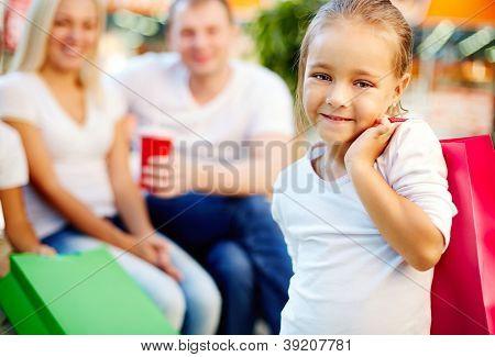 Retrato de menina feliz segurando paperbag e olhando para câmera no shopping com os pais no fundo