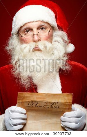 Portrait of Santa Claus holding Christmas letter in his hands and looking at camera