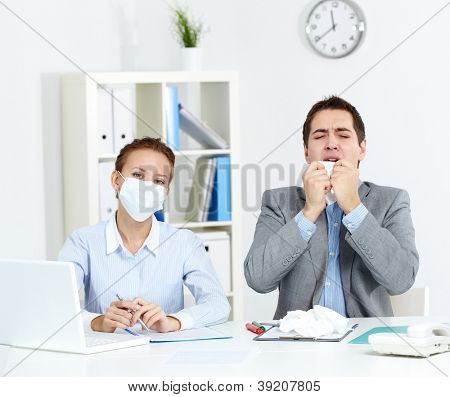 Image of sick businessman with tissue sneezing with his colleague in mask sitting near by and looking at camera in office