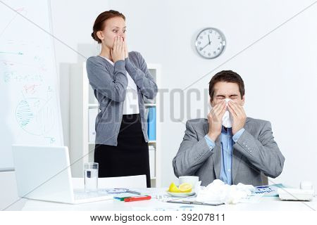 Image of businessman sneezing while his partner looking at him with fright in office