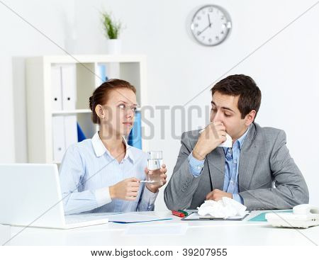 Image of sick businessman looking at his partner giving him tablets and water in office