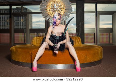 Sexy young woman sitting on round sofa with black mini feather dress and pink high heels