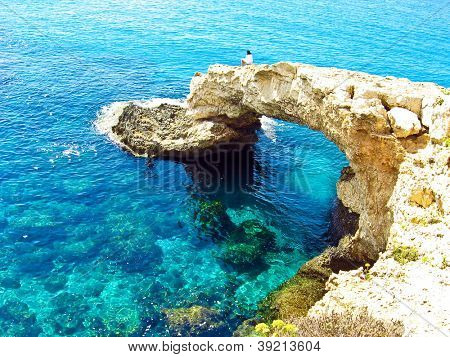 Panoramic view to a rocky beautiful coast among blue bright transparent water of the sea with sky reflection in sunny day