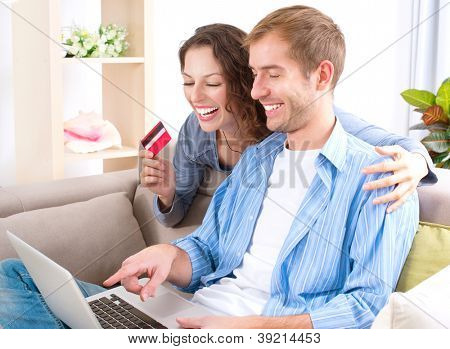 Online Shopping.Happy Smiling Couple Using Credit Card to Internet Shop on-line. Young couple with Laptop Computer and Credit Card buying online. Christmas and New Year Gifts. e-shopping . ecommerce