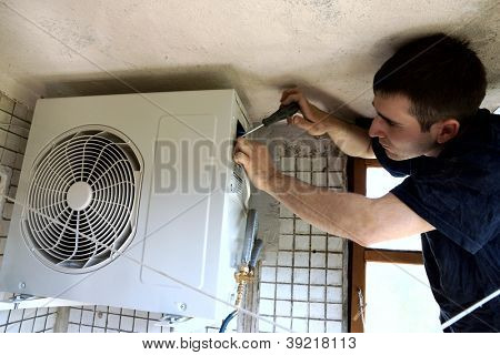 real photo of installation of the conditioner, the worker connects electric wires