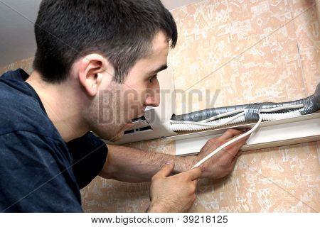 foto real de la instalación del acondicionador, el trabajador conecta los cables eléctricos