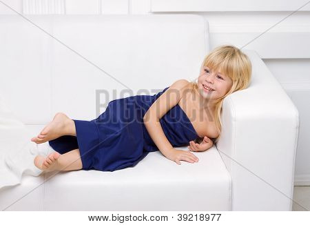 3 years old girl is in a blue dress on a white sofa