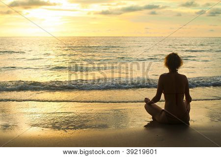 A relaxed sexy young girl wearing a bikini sitting on a deserted tropical beach at sunset.