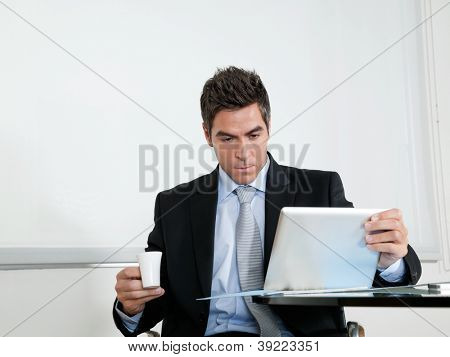 Handsome young businessman with coffee cup using digital tablet at desk in office