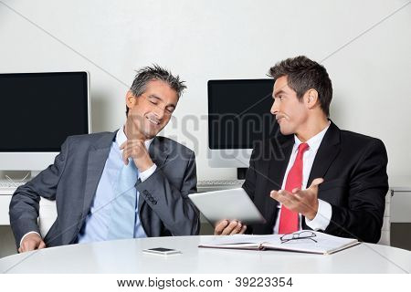 Young businessman holding digital tablet sitting with colleague at desk in office