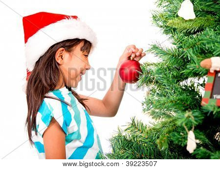 Happy girl decorating the Christmas tree with beautiful ornaments
