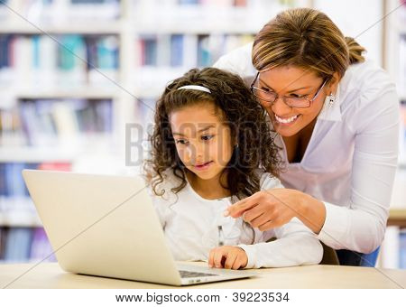 Schoolgirl researching online with the guidance of her teacher