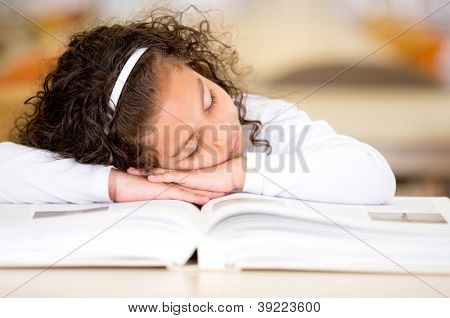 Tired girl falling asleep after reading a book