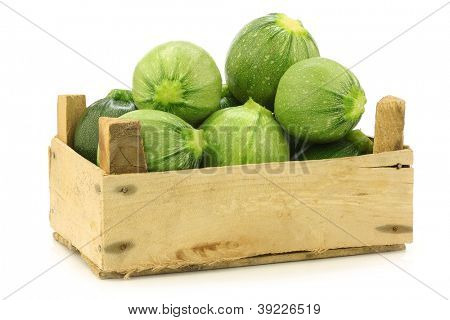 mixed light green and green zucchini's (Cucurbita pepo) in a wooden crate on a white background