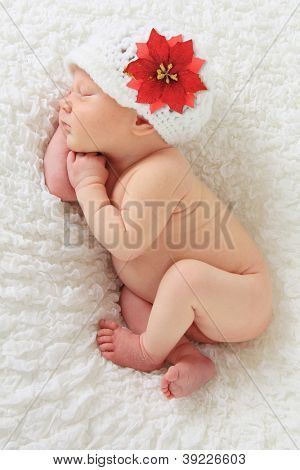 Newborn Christmas baby girl asleep on a blanket.