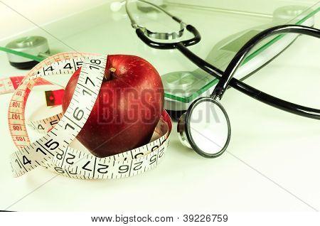 apple, tape measure, scale, stethoscope