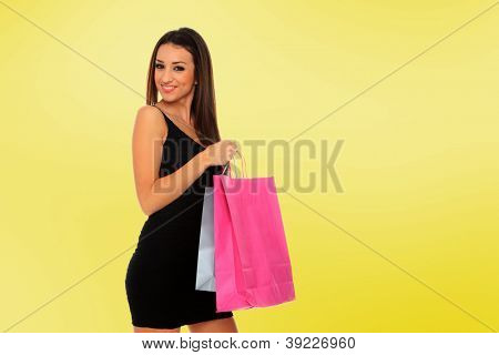 A shot of a woman with bags shopping over yellow background