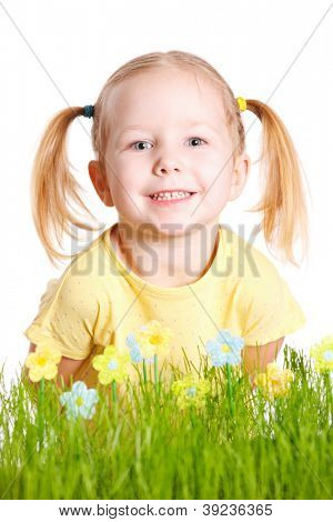 Studio portrait of adorable little girl behind fresh green grass