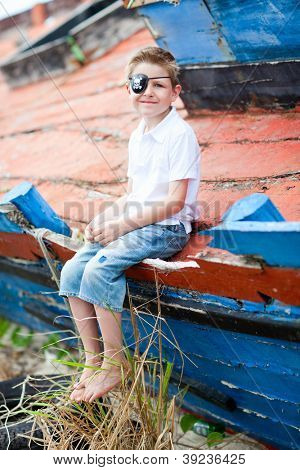 Outdoor portrait of cute pirate boy sitting at an old boat