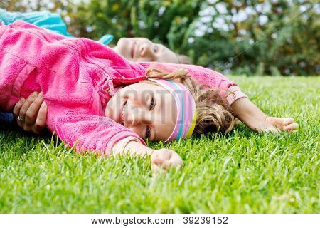 Happy little girl lying on grass, her mother behind