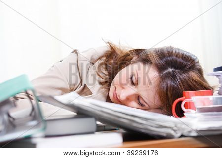 Businesswoman sleeping among papers and coffee cups