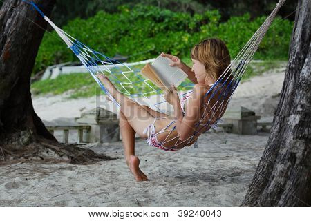 Young woman reading a book lying in a hammock on tropical resort