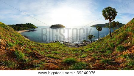 Panorama of tropical coast with beach,  palm trees and island in calm blue sea. Ya Nui beach (left sandy coast) of Phuket. Thailand
