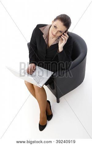 Businesswoman working, using mobile phone and laptop computer, sitting in armchair, looking up smiling, elevated view.