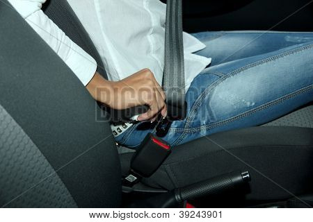 driver fastening seat belt in car