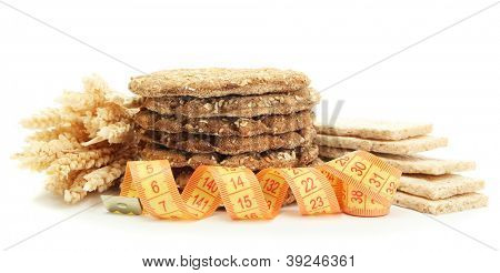 tasty crispbread, measuring tape and ears, isolated on white