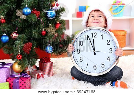 Little boy with clock in anticipation of New Year