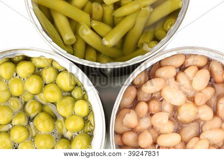 Open tin cans of french bean, beans and peas isolated on white