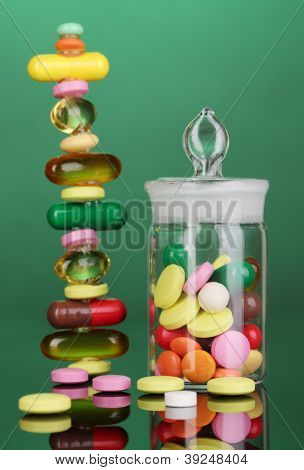 Capsules and pills hill and in receptacle on green background