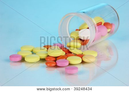 Pills in receptacle on blue background