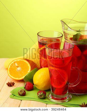 sangría en la jarra y vasos con frutas, en la mesa de madera, sobre fondo verde