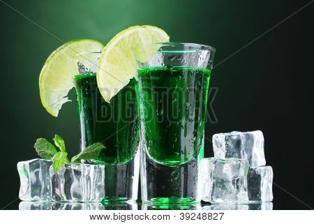 Two glasses of absinthe, lime and ice on green background